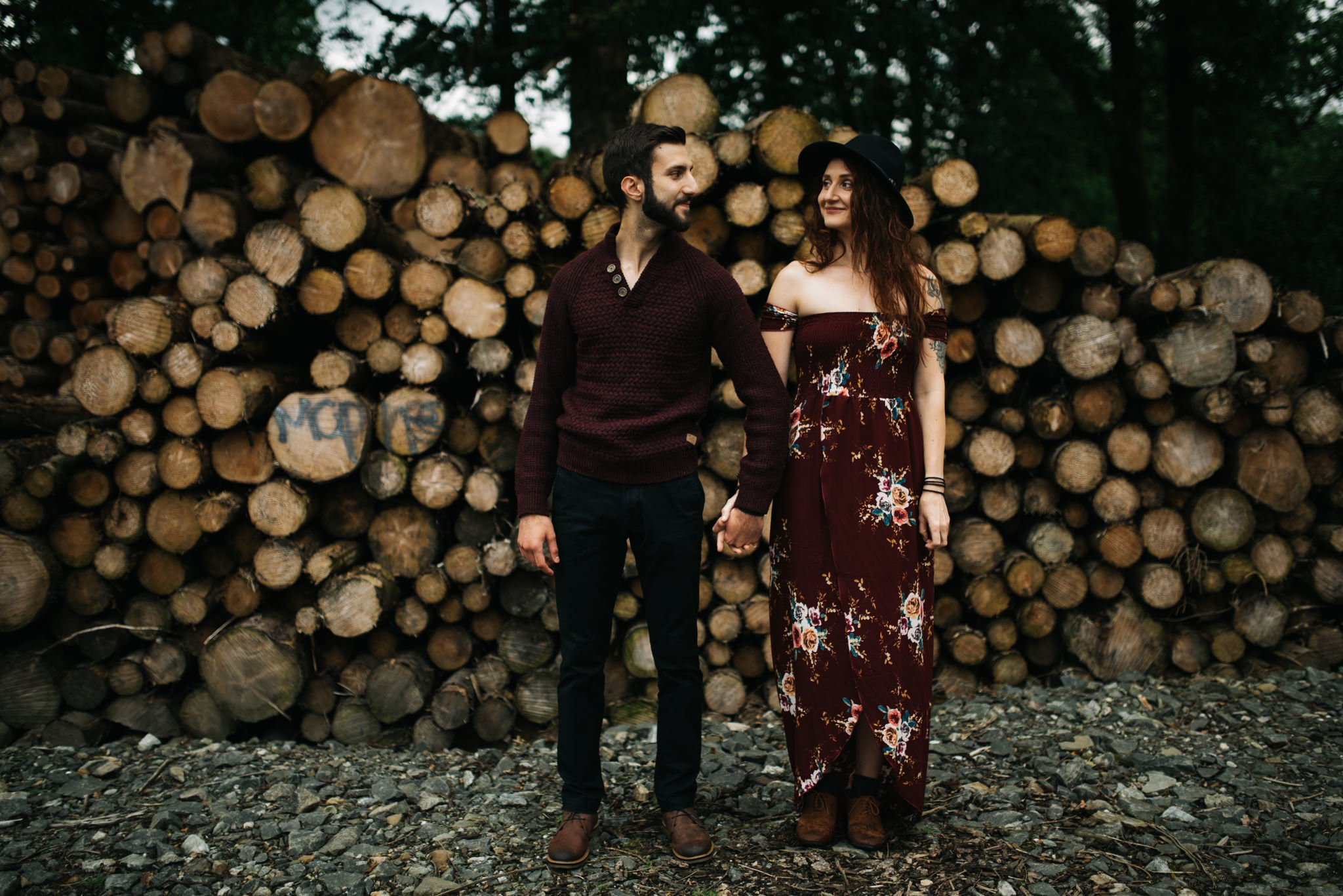 couple holding hands with logs in background