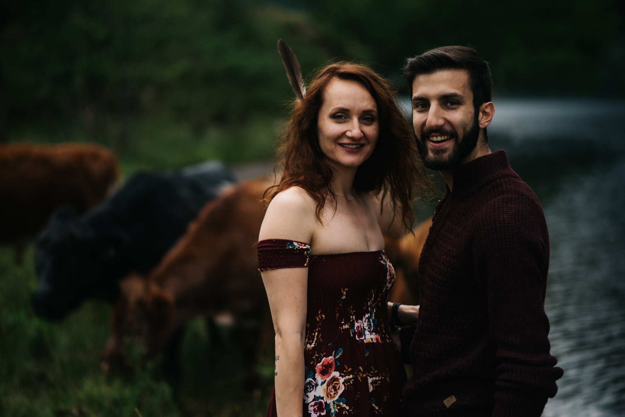 couple smiling with cows in background