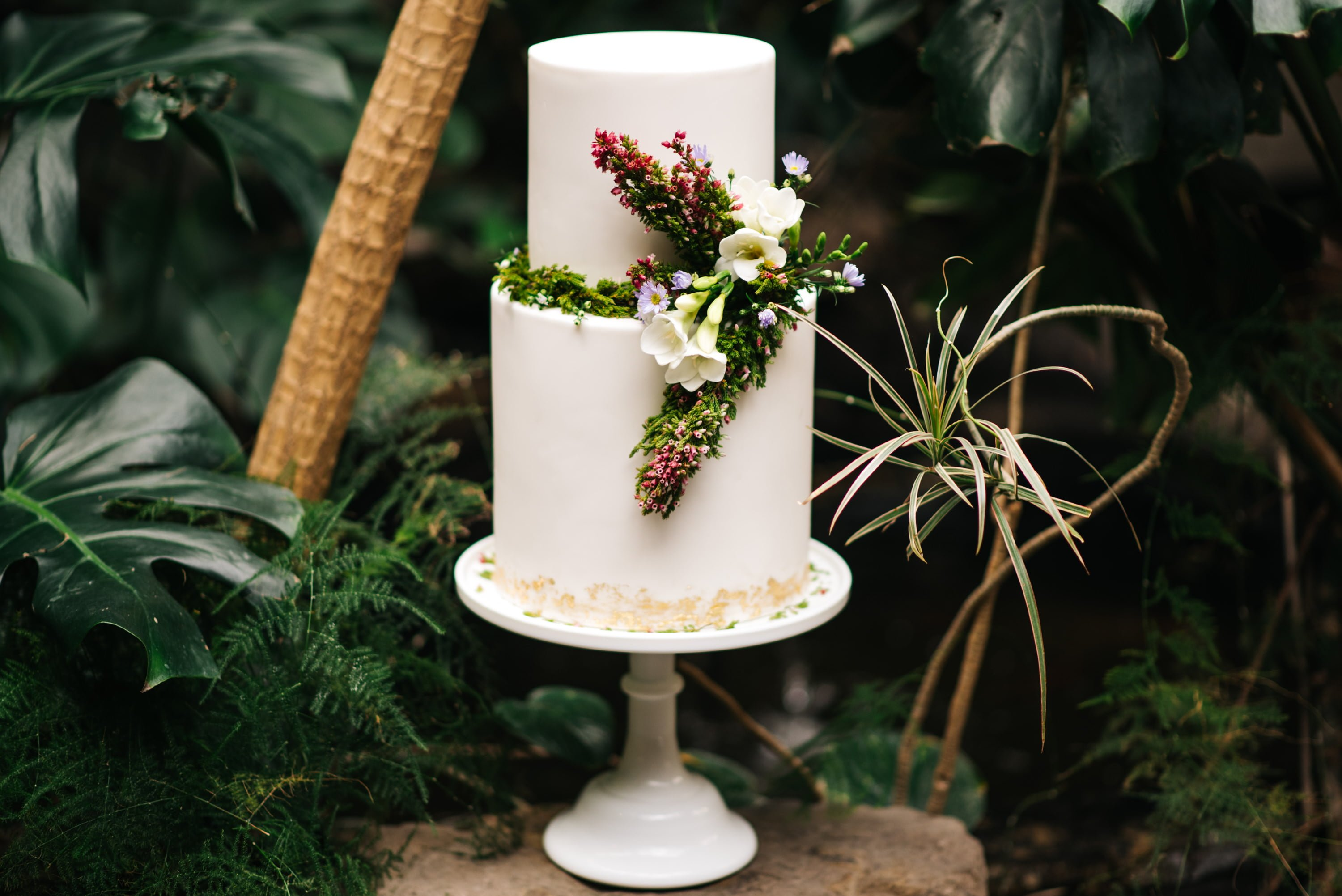 wedding cake with cake stand and foliage