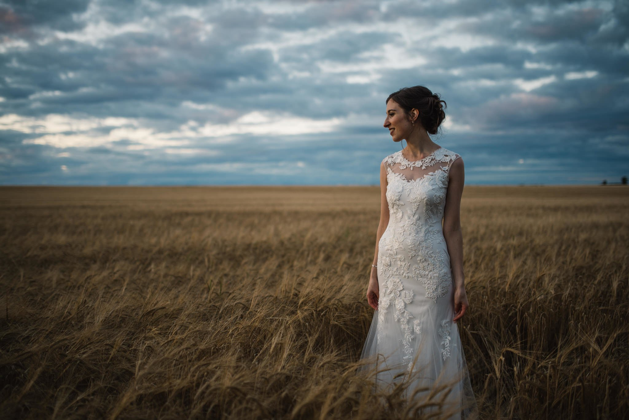 bride in barley field with evening sky