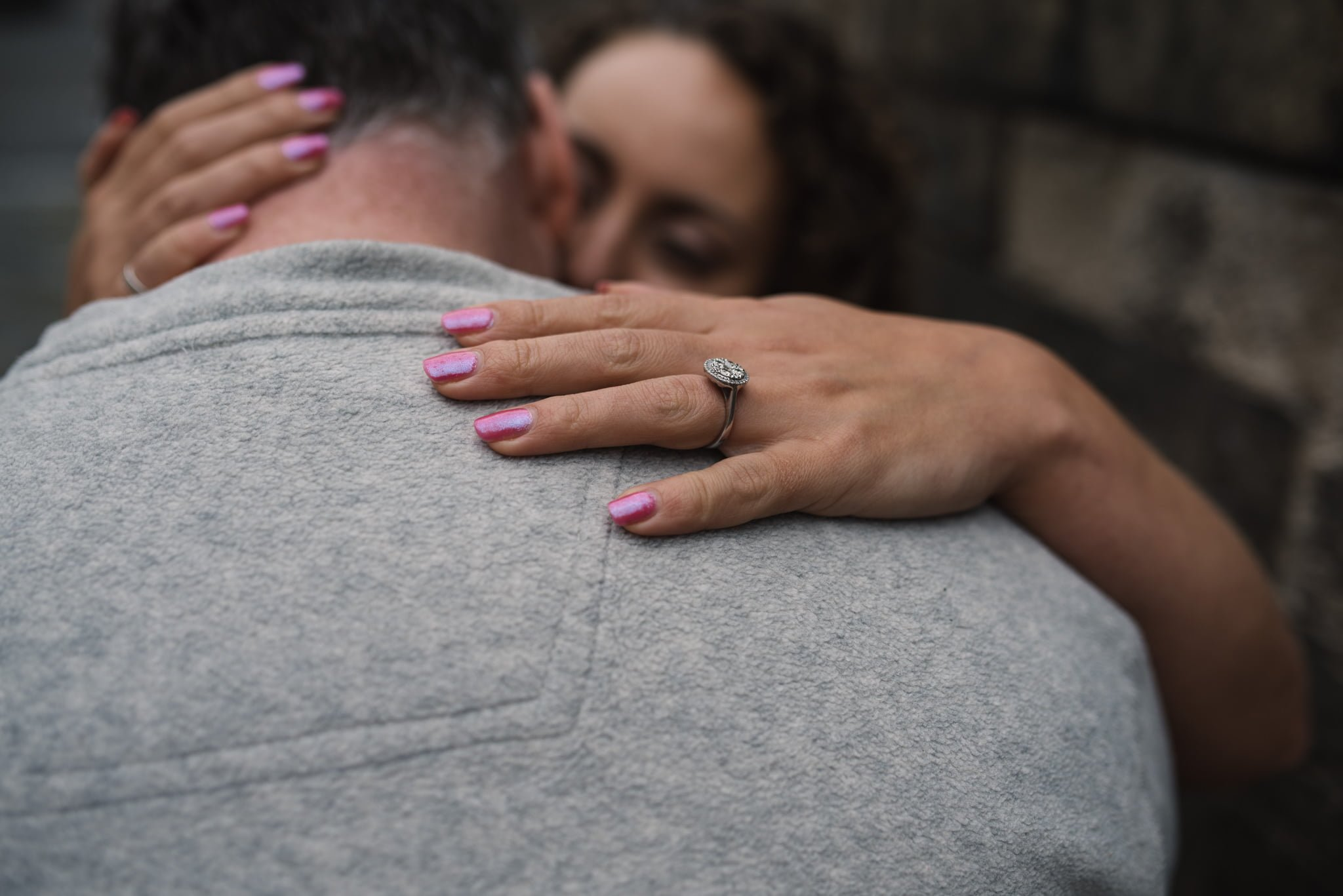 couple embracing with engagement ring