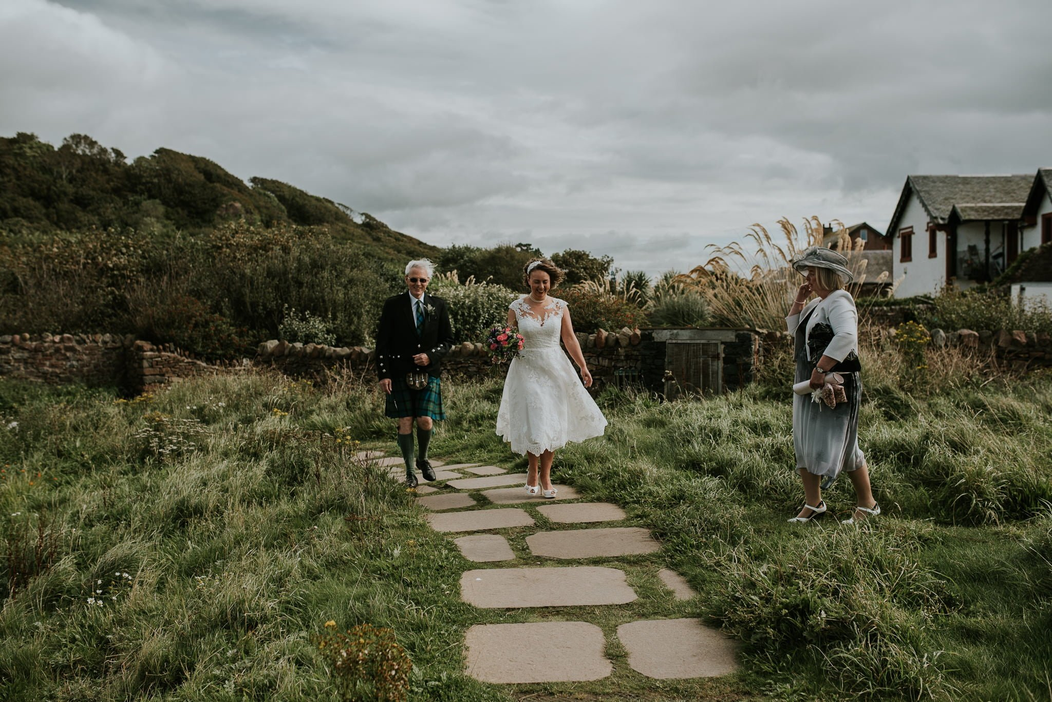 bride and father walking towards portencross castle
