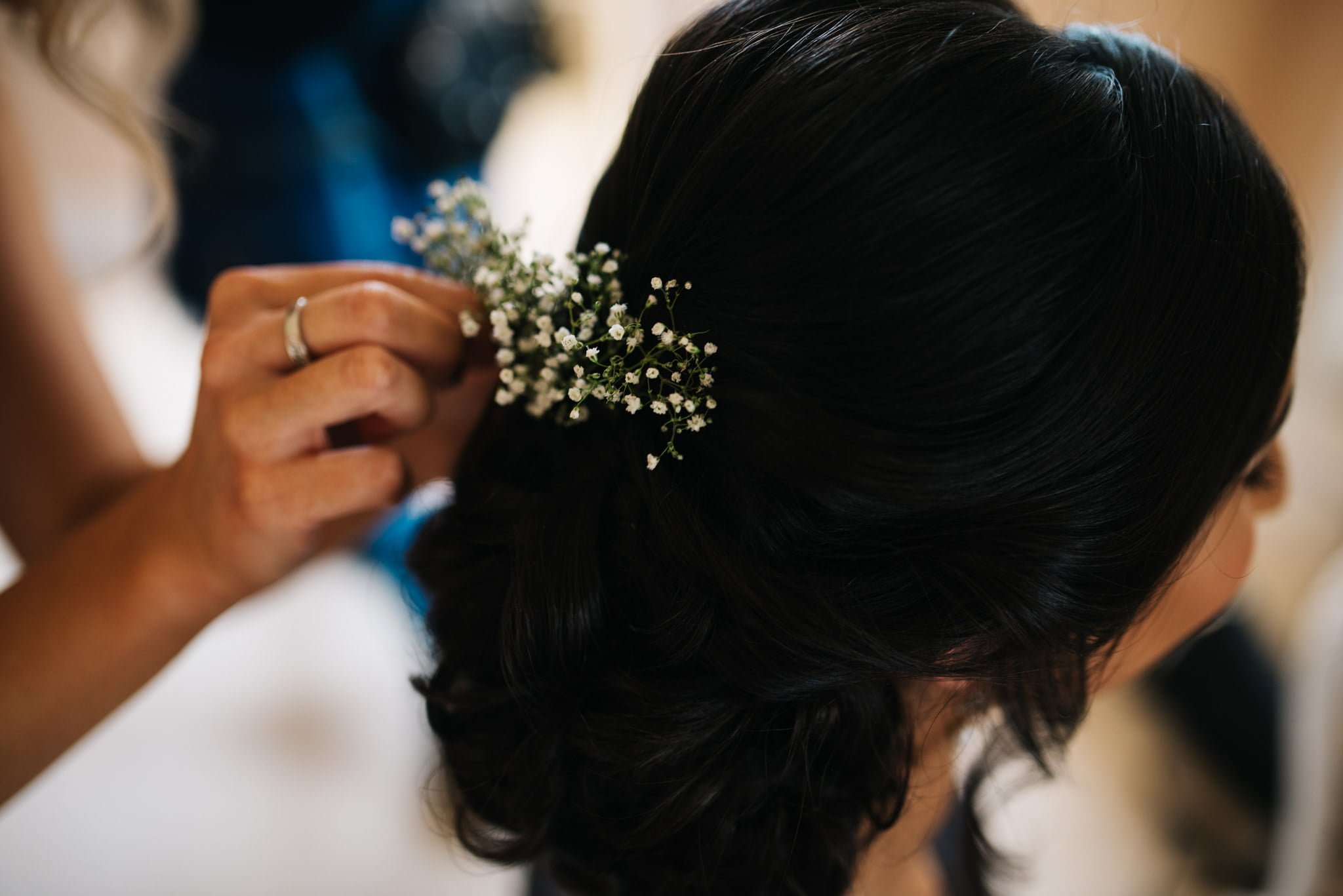 bride getting flowers attached to her hair