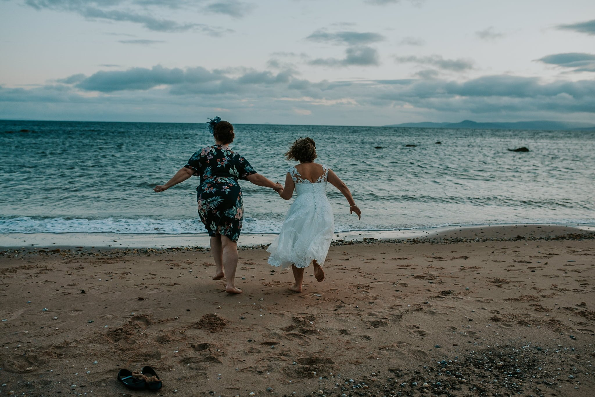 bride and bridesmaid running towards the sea