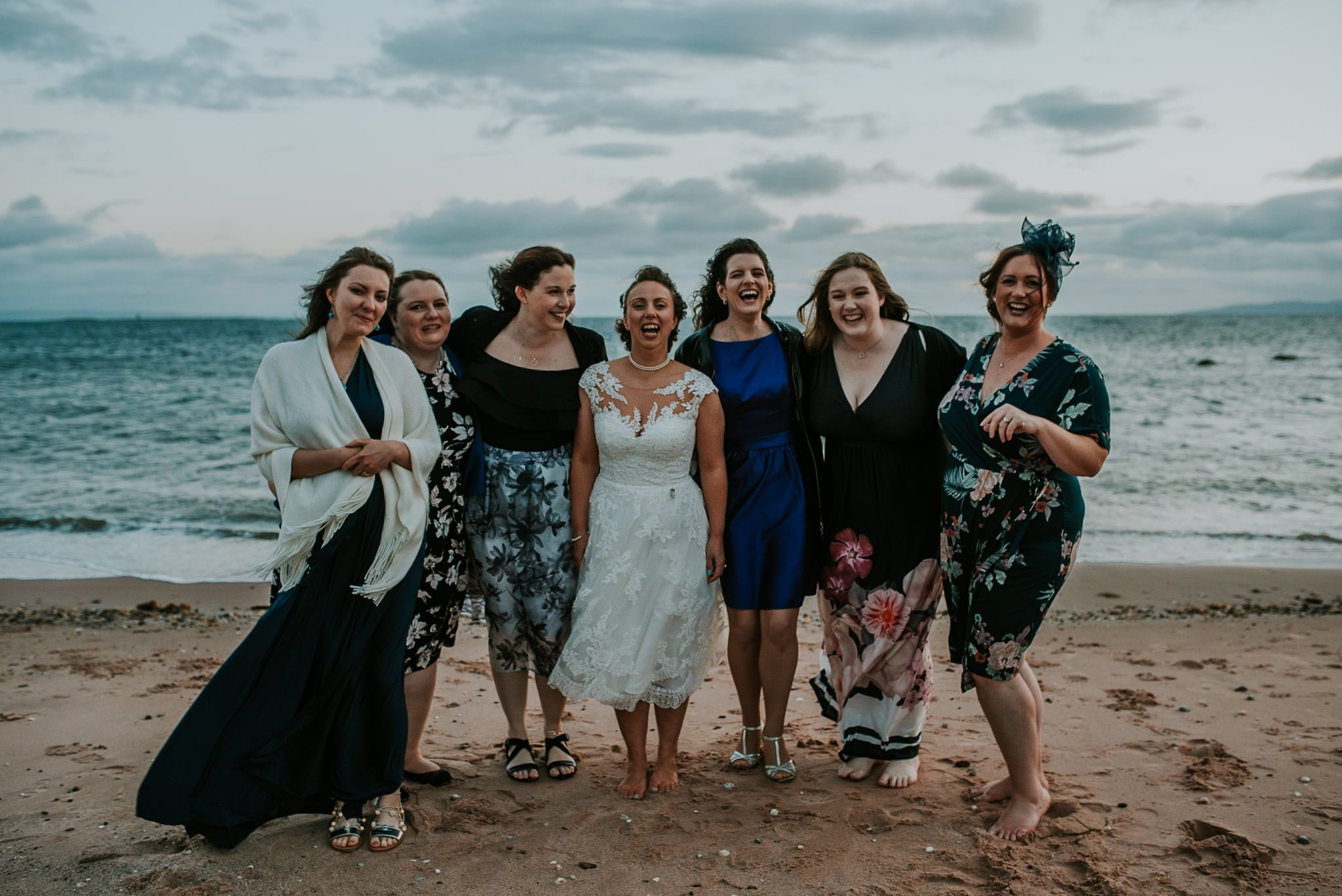 bride with bridesmaids on the beach