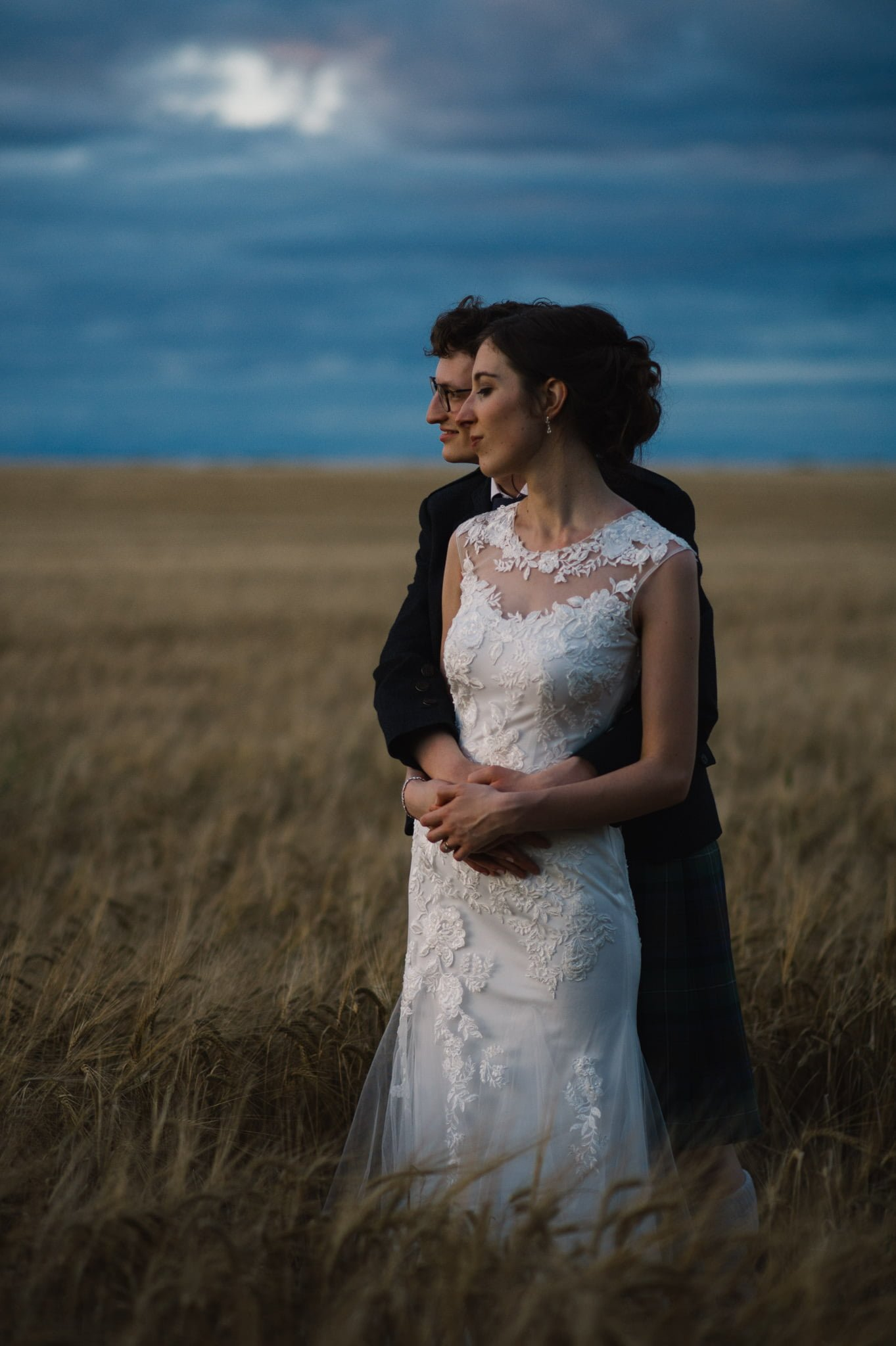 couple in barley field with evening skies
