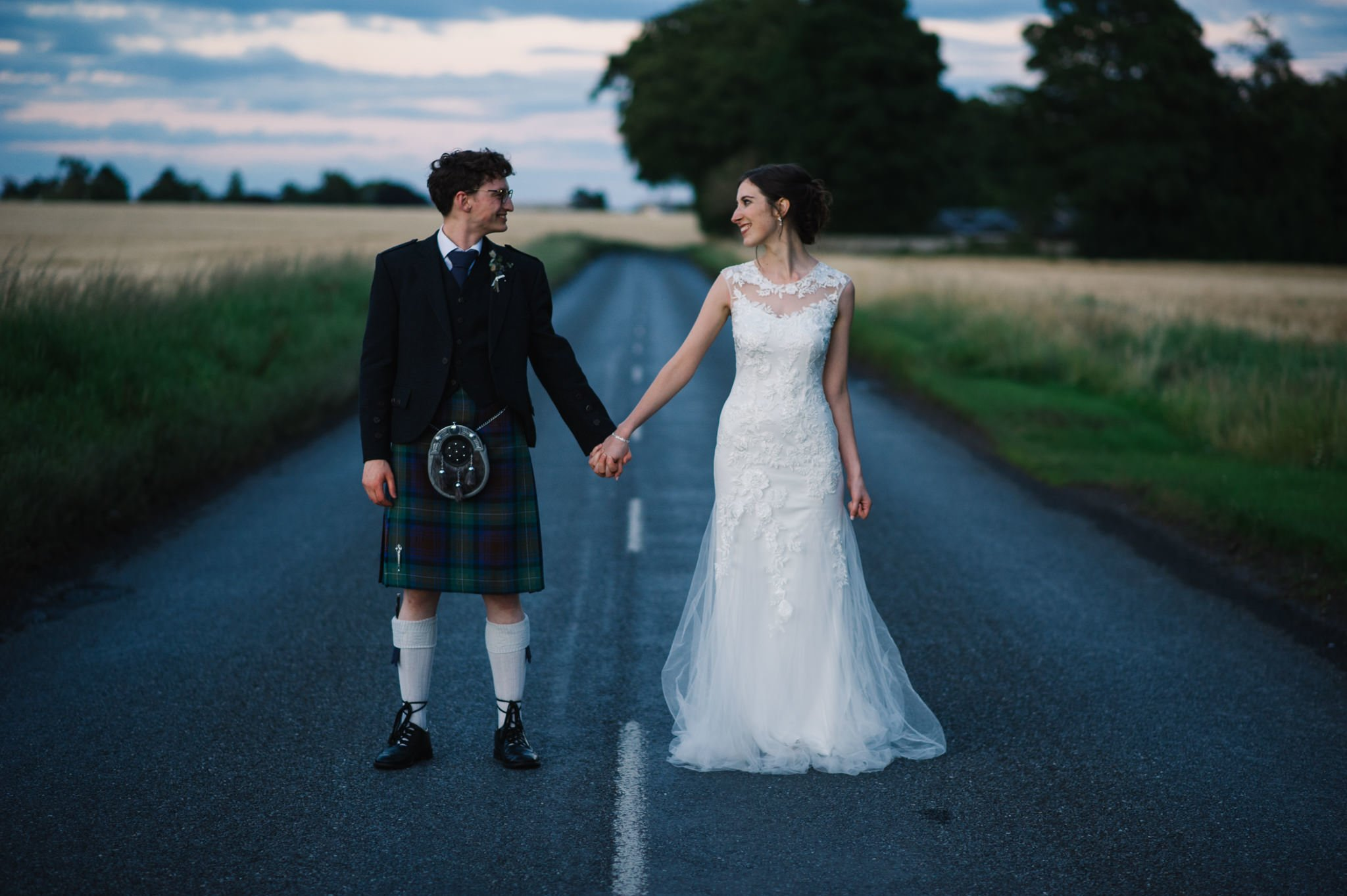 bride and groom holding hands on a country road