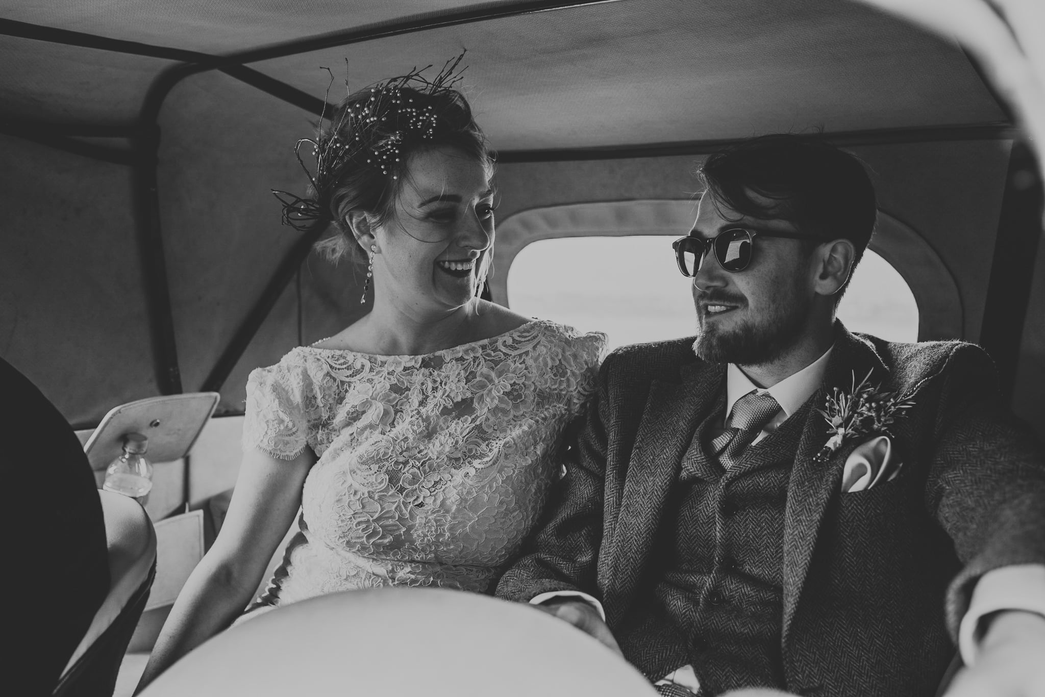 couple inside vintage wedding car