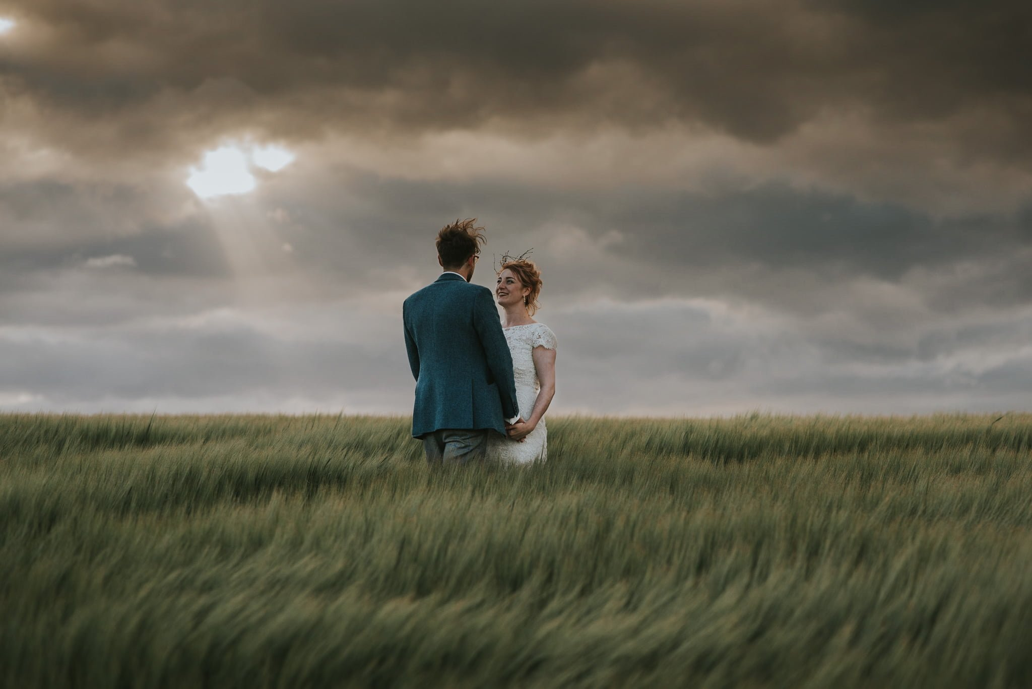 couple in barley field sun breaking through clouds
