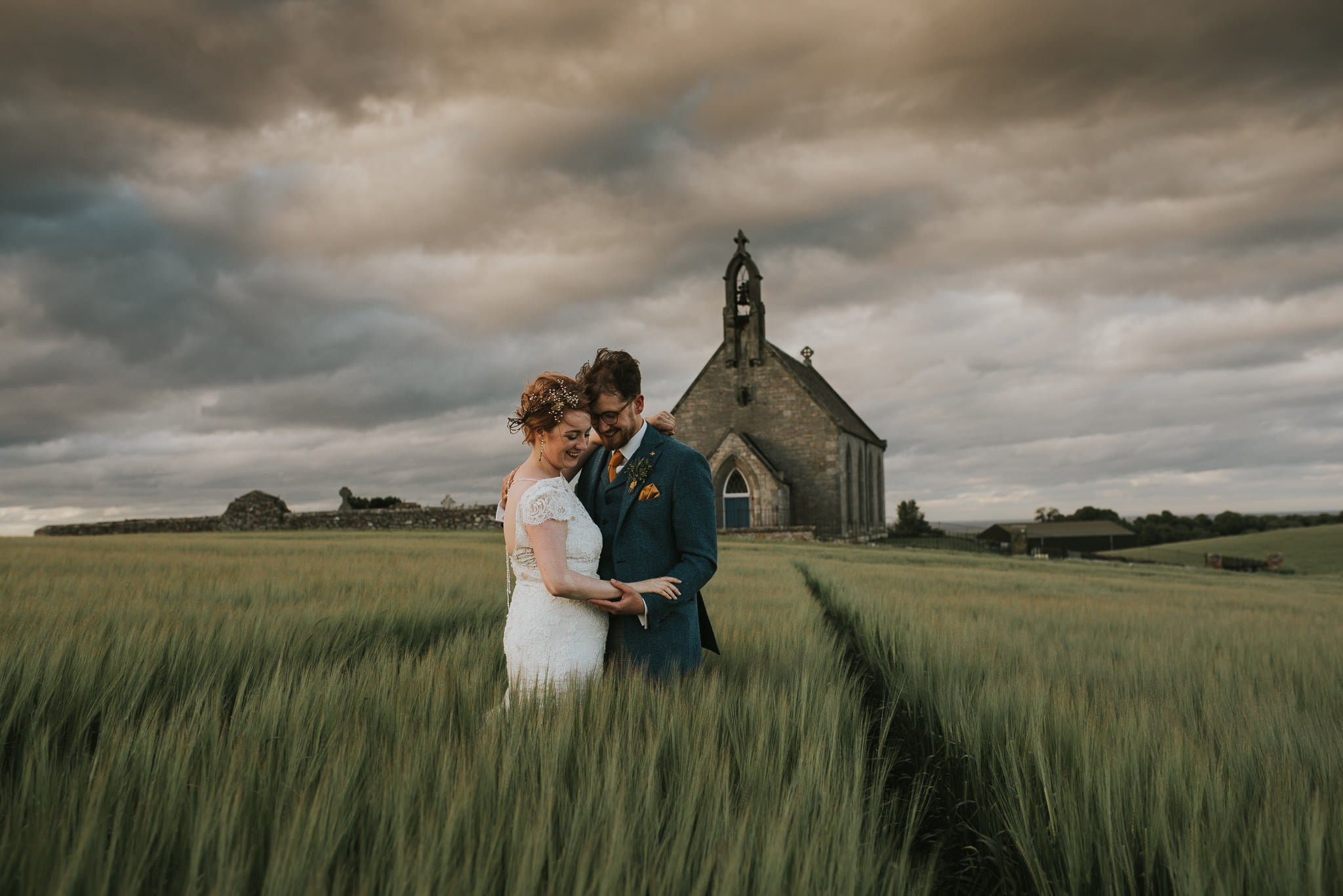 couple in barley field with chapel
