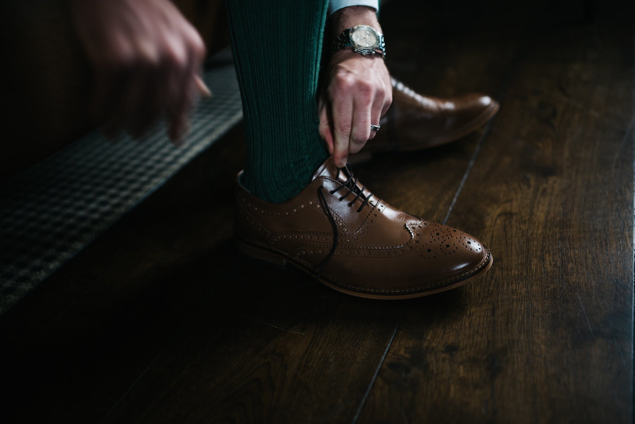 groom tying the laces of his brogues