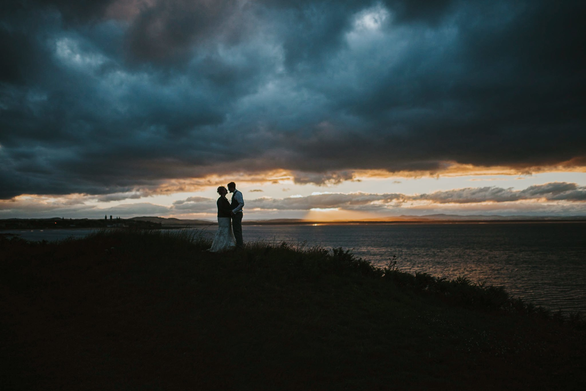 couple with dramatic evening skies over st. andrews