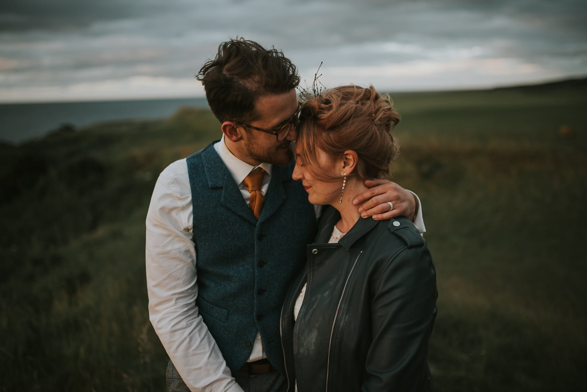 couple by the sea embracing bride wearing leather jacket