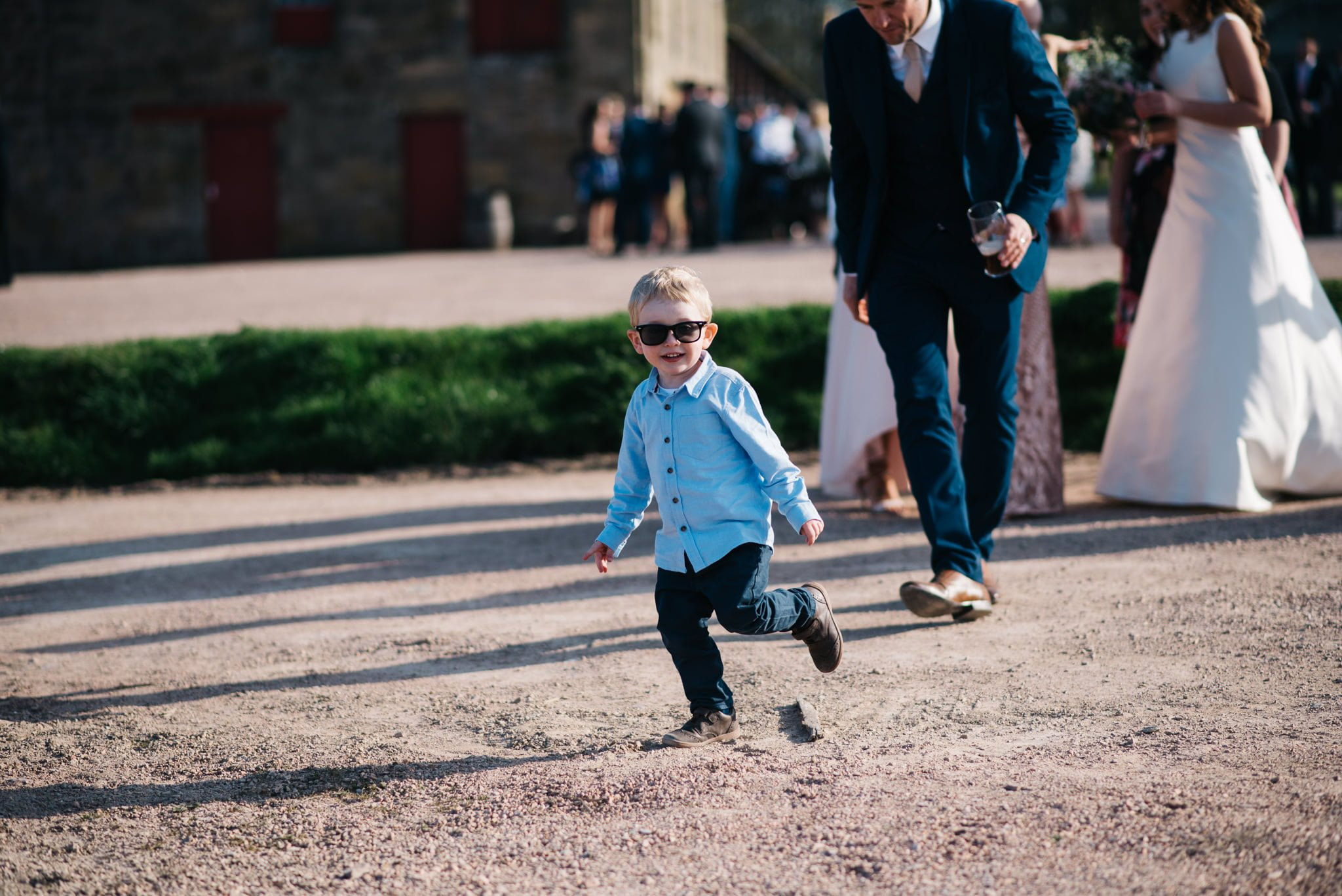 boy with sunglasses running at wedding