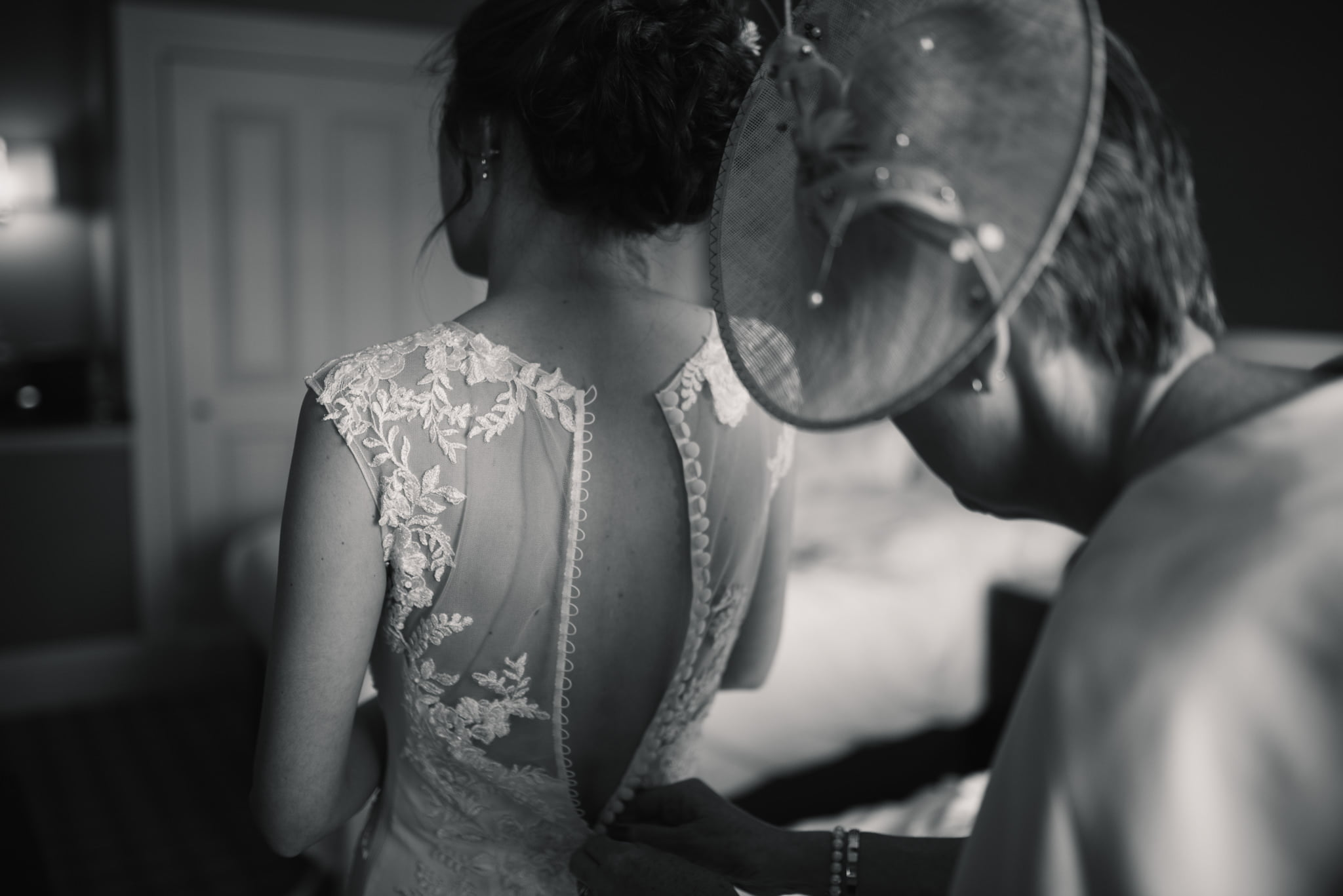 mother helping bride into her dress
