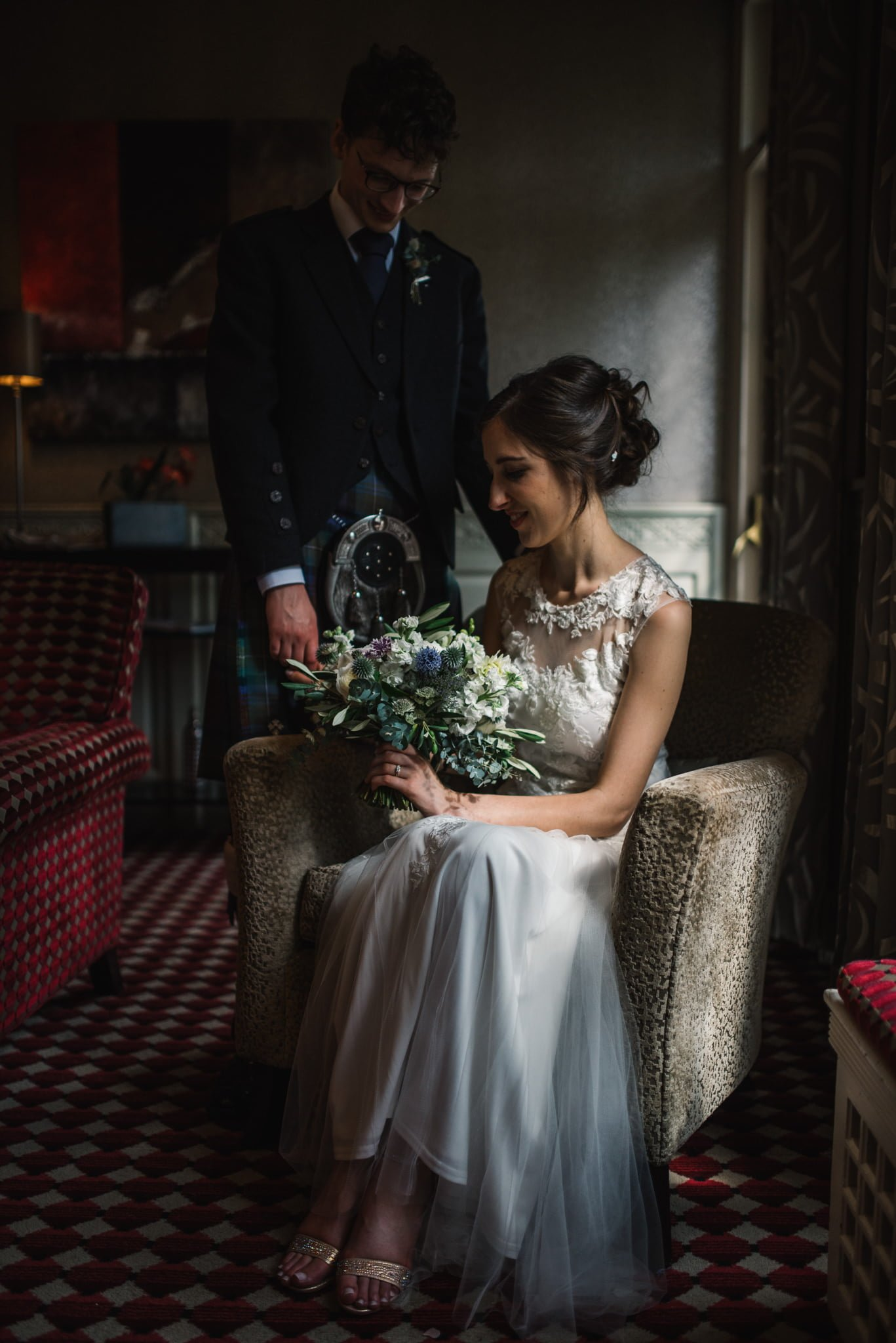 bride sitting with groom standing