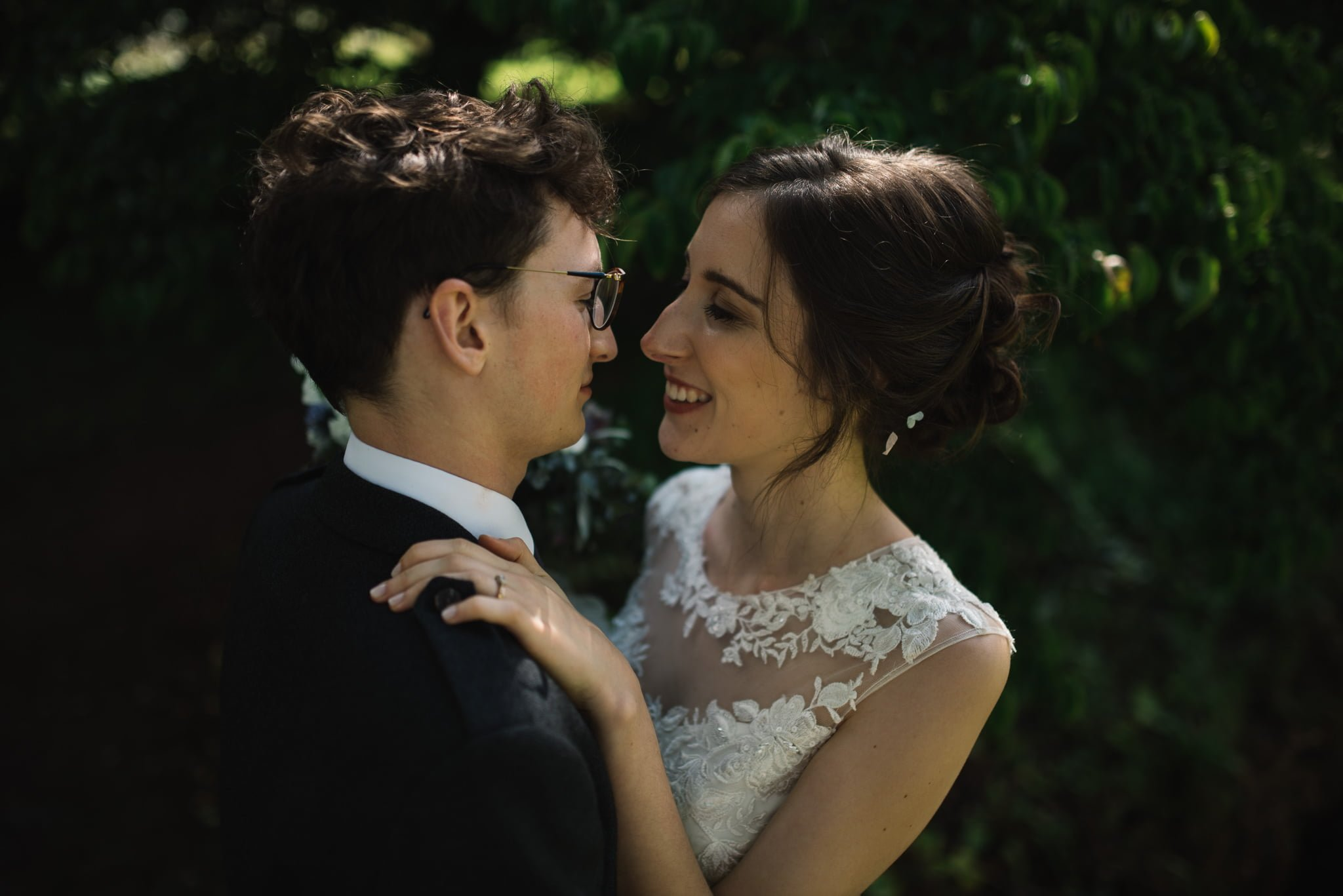 wedding couple embracing her hand on his shoulder