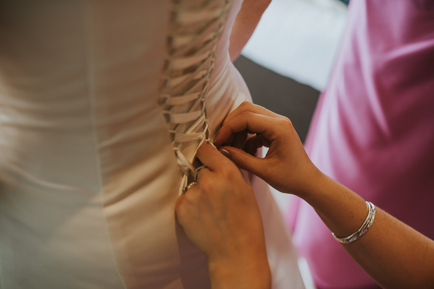 country wedding bridesdress being buttoned up