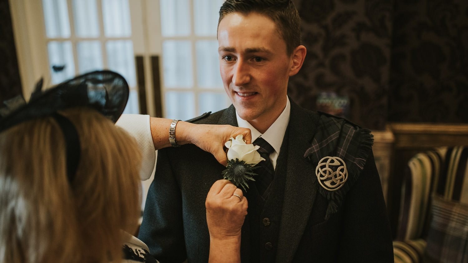 country wedding groom getting buttonhole fitted