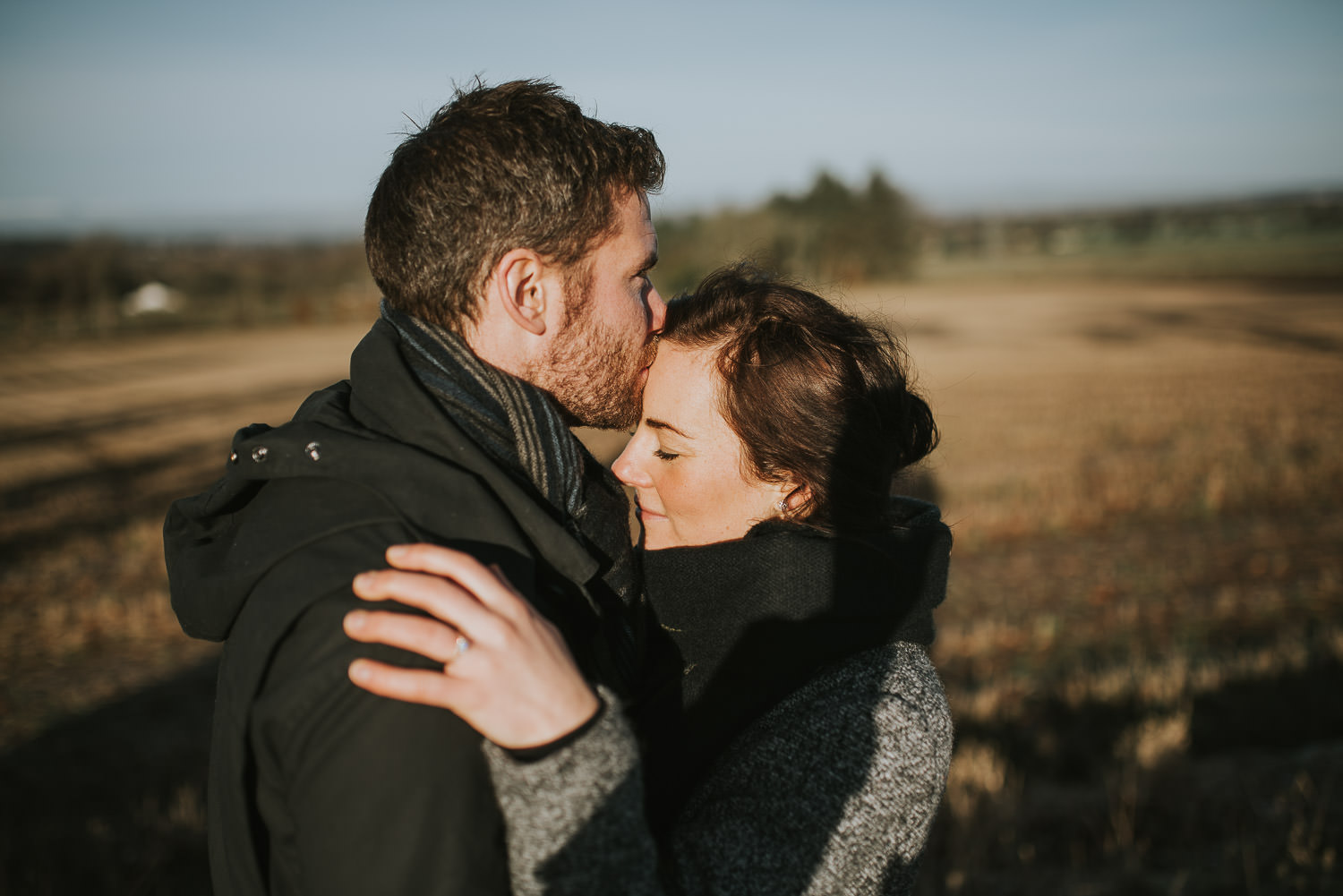 man kissing woman on the forehead in a field