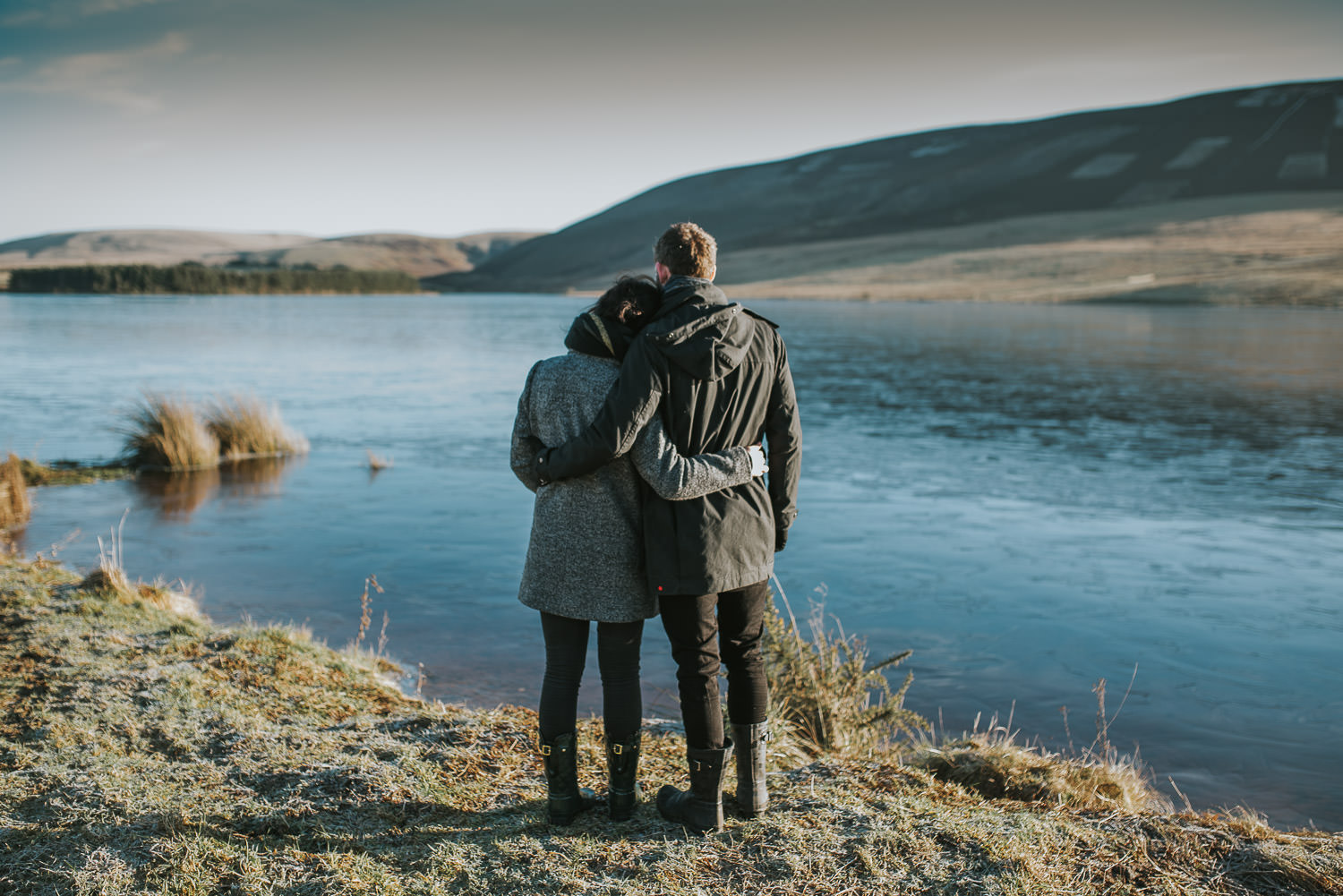 couple standing arm in arm at the shores of a frozen over reservoir