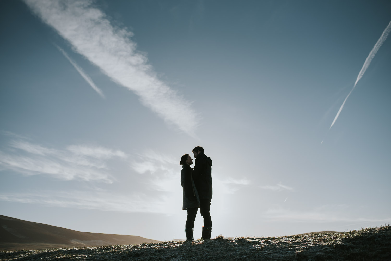 couple backlit by the sun against a blue winter sky