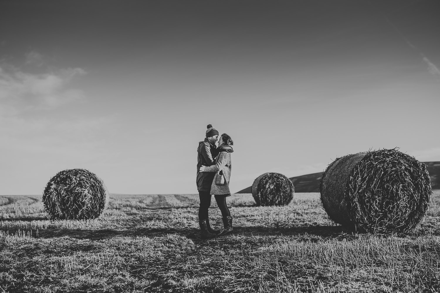 couple hugging in a field with straw bailes