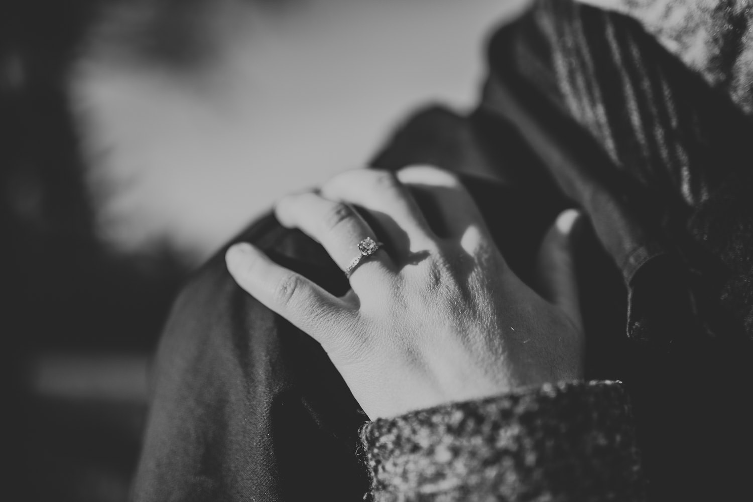 woman's hand with engagement ring resting on man's shoulder