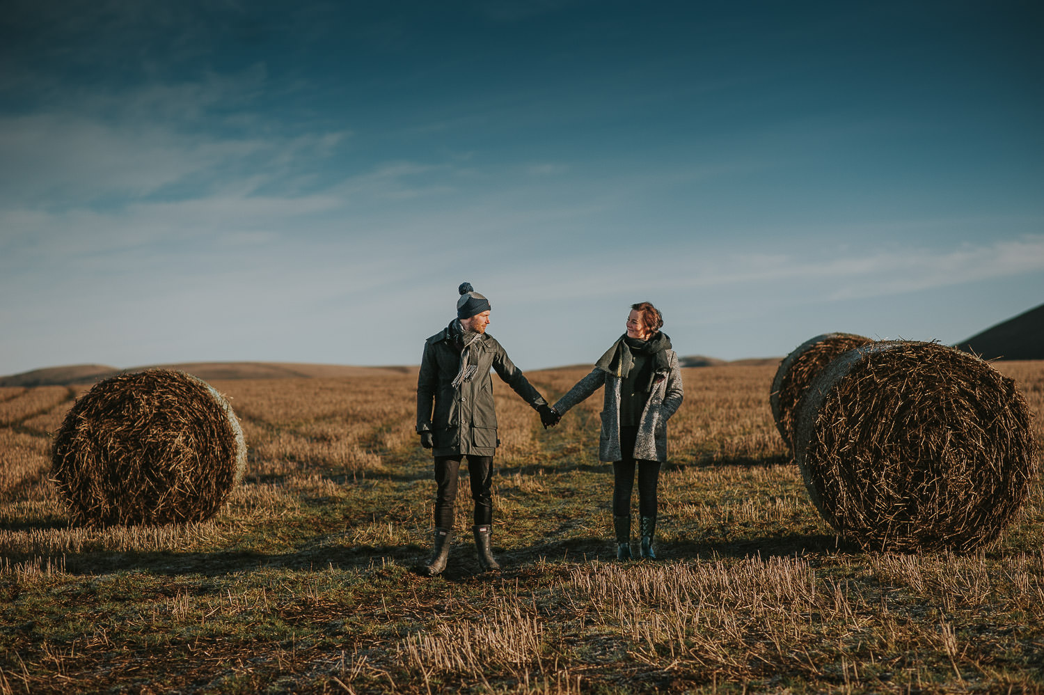 couple holding hands in a field with straw bails