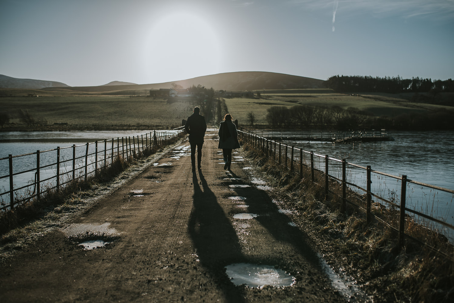 couple walking along an ice covered footpath at a reservoir
