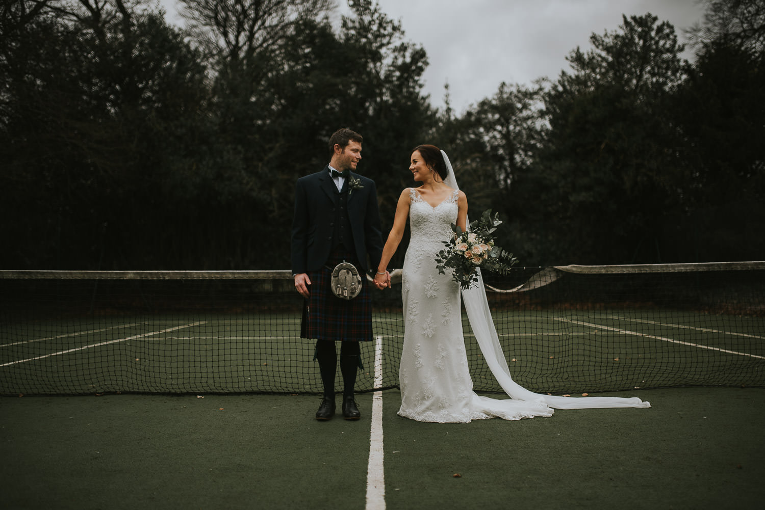 Bride and groom on the tennis court holding hands