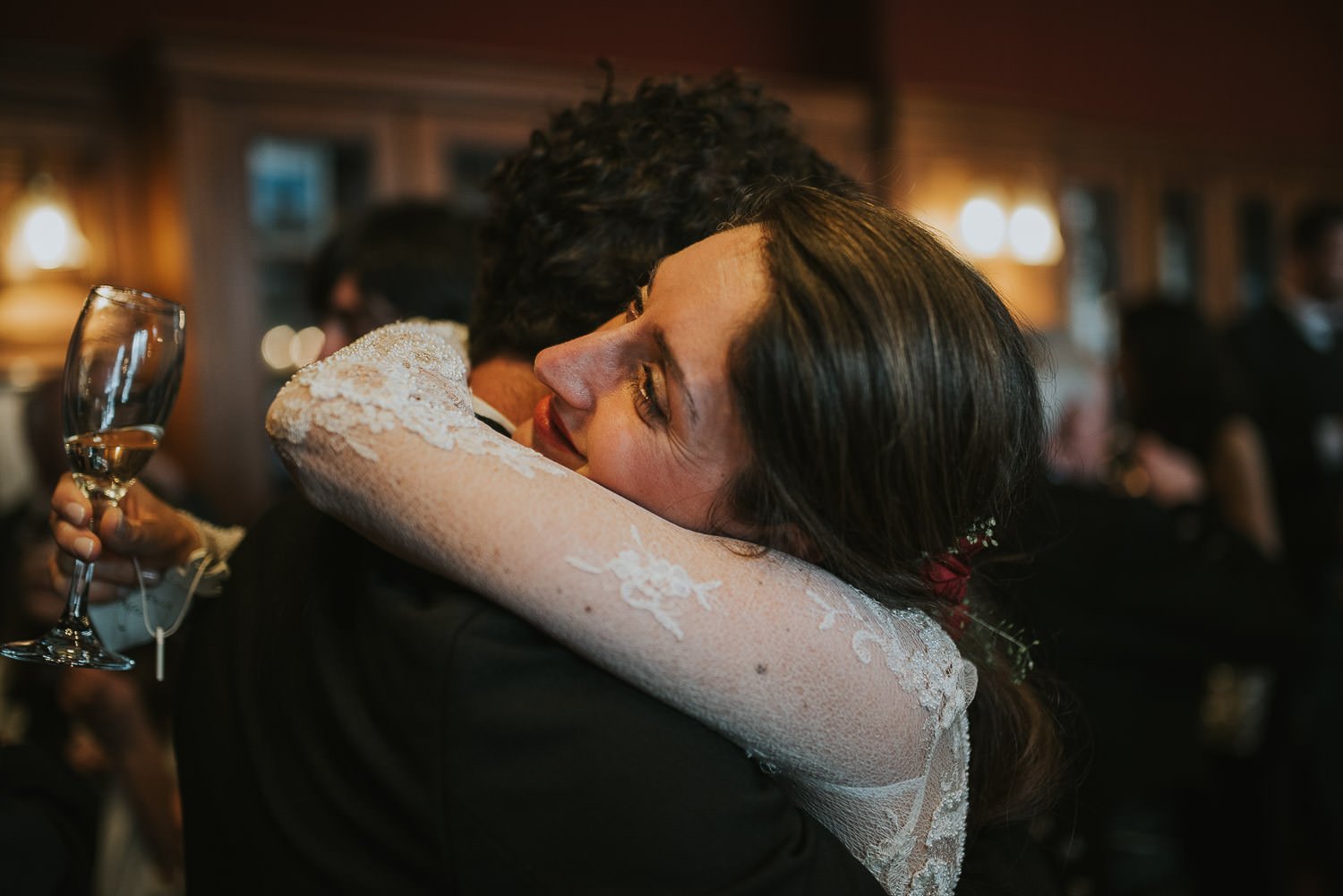 bride hugs guest at wedding reception