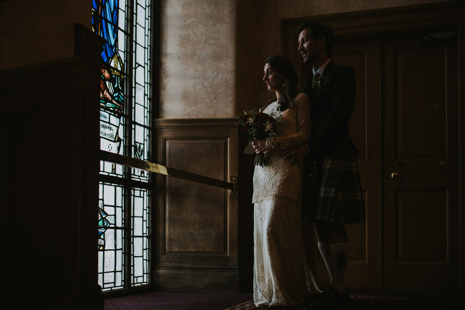 bride and groom standing at stained glass window