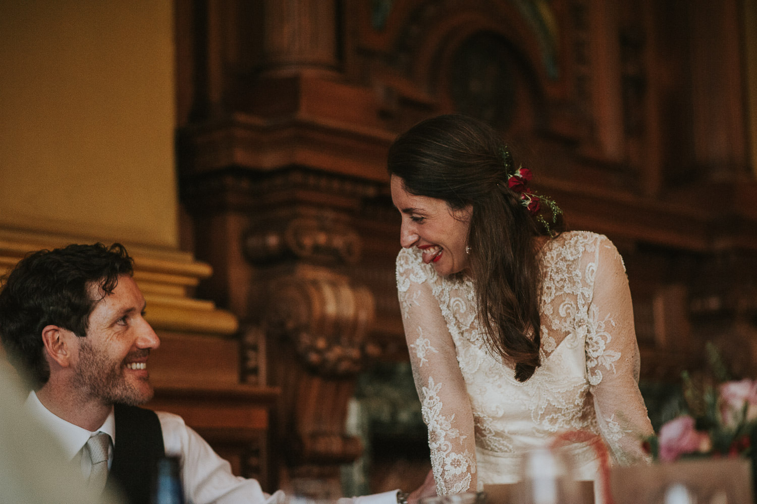 bride and groom smiling at each other during speeches