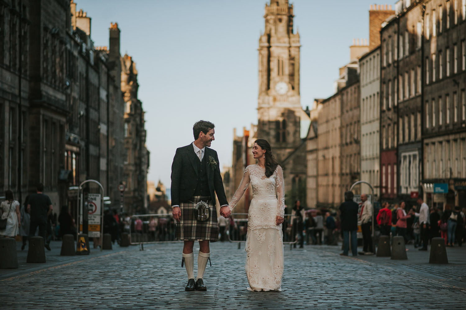 bride and groom on Royal Mile holding hands