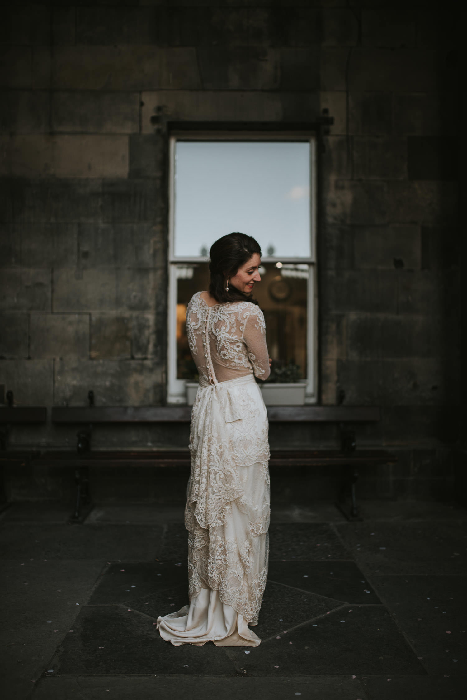 bride in vintage wedding dress looking over her shoulder
