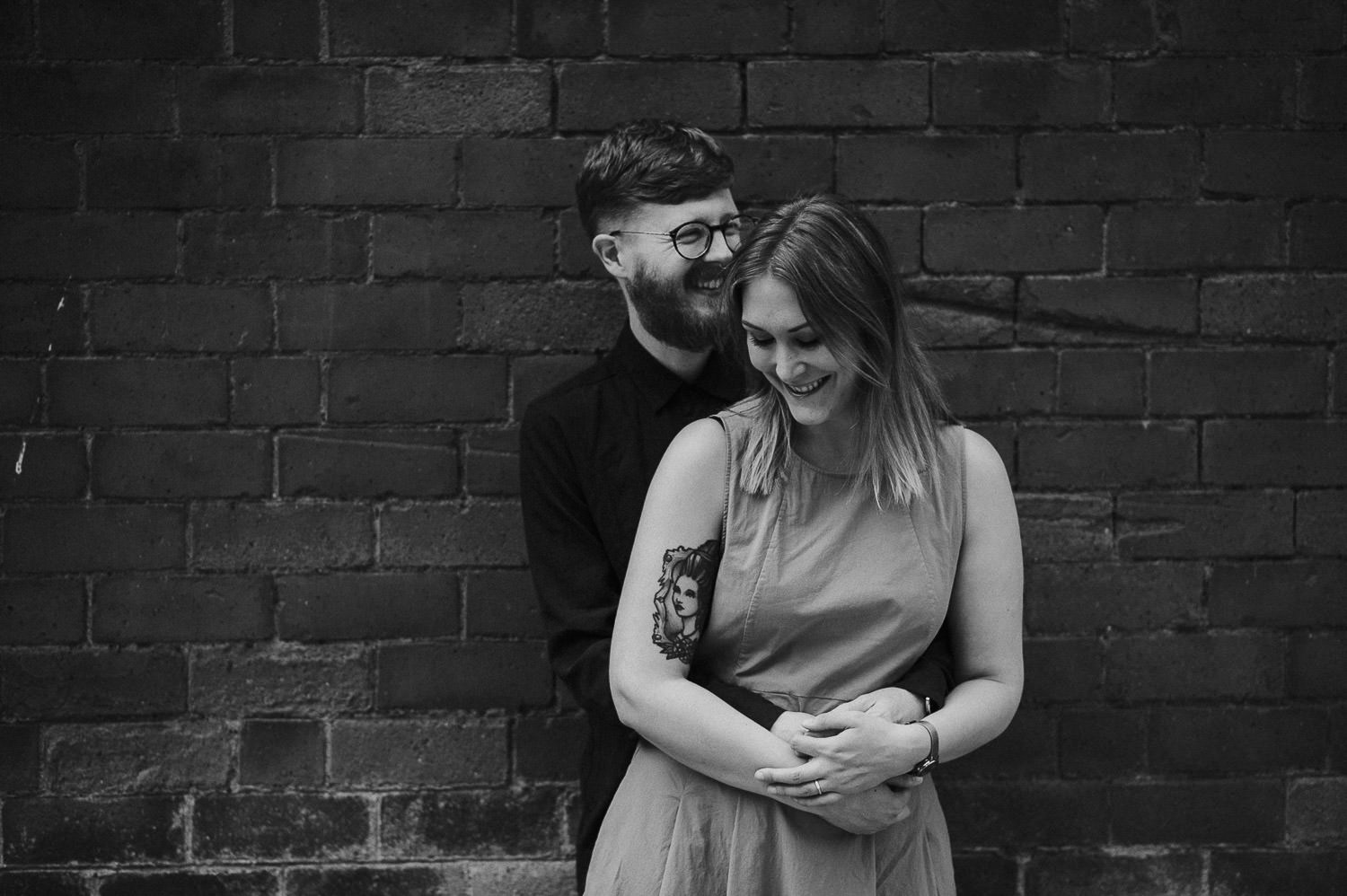 couple embracing in front of a brick wall