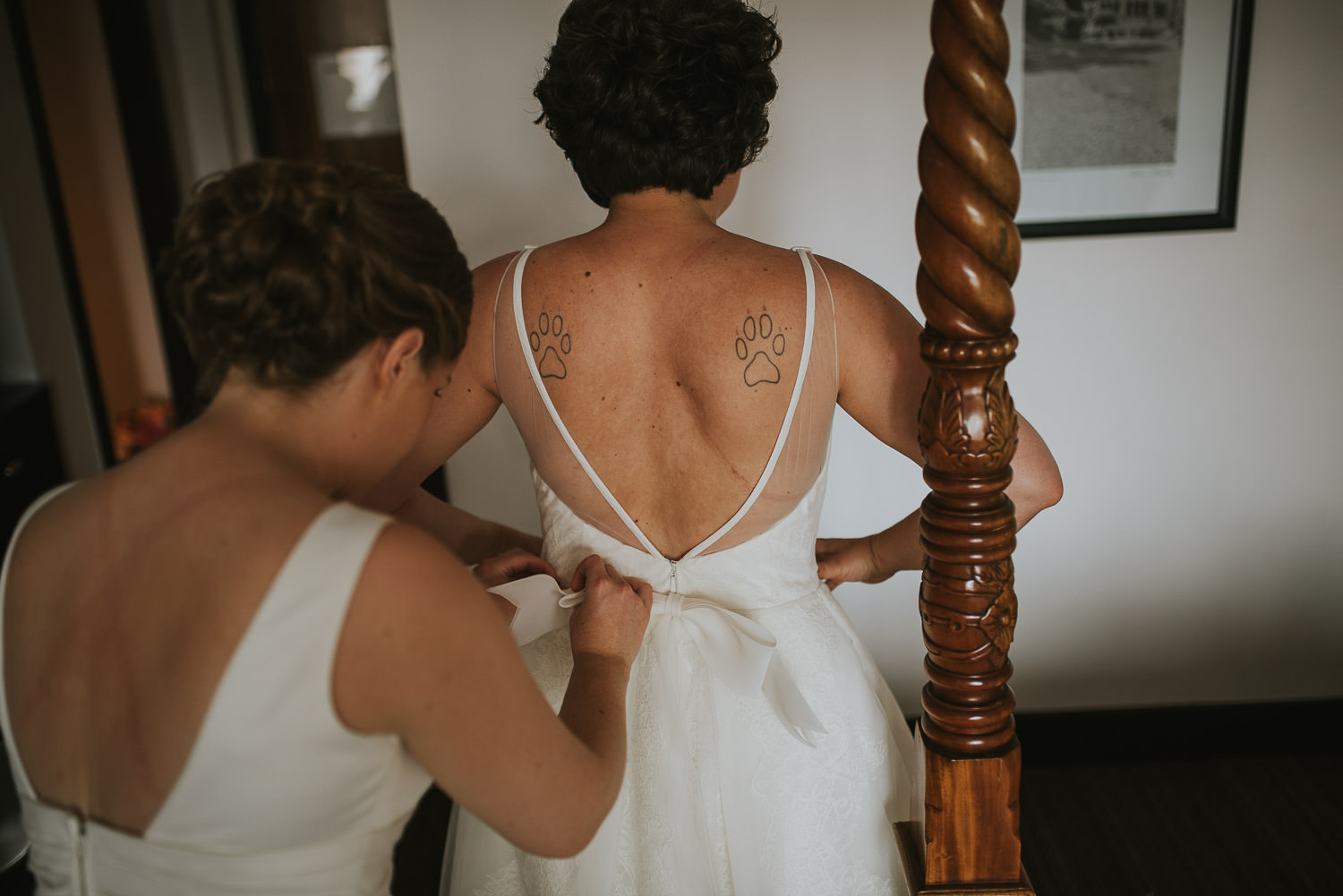 bride helping other bride into her wedding dress