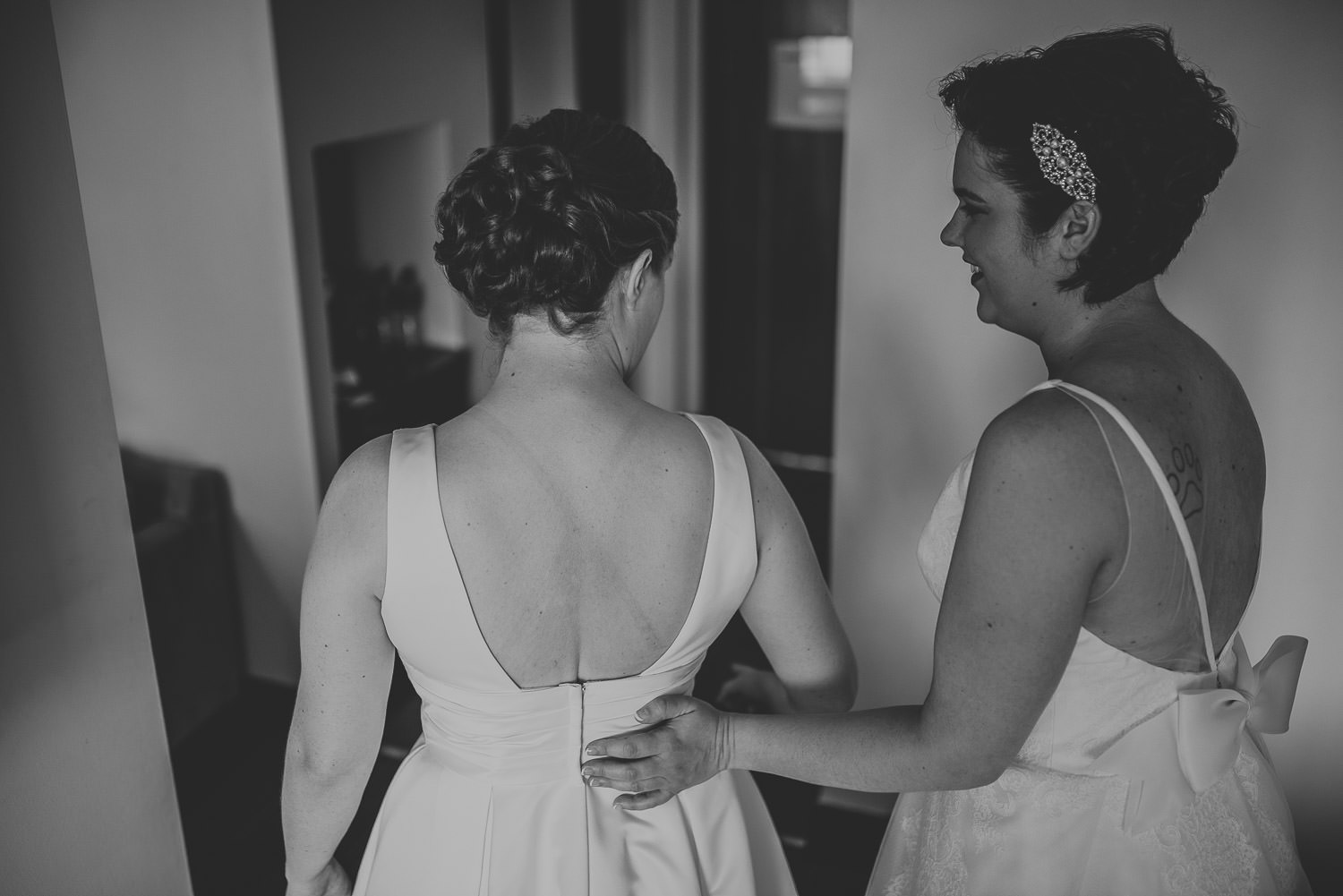 bride helping other bride into her dress