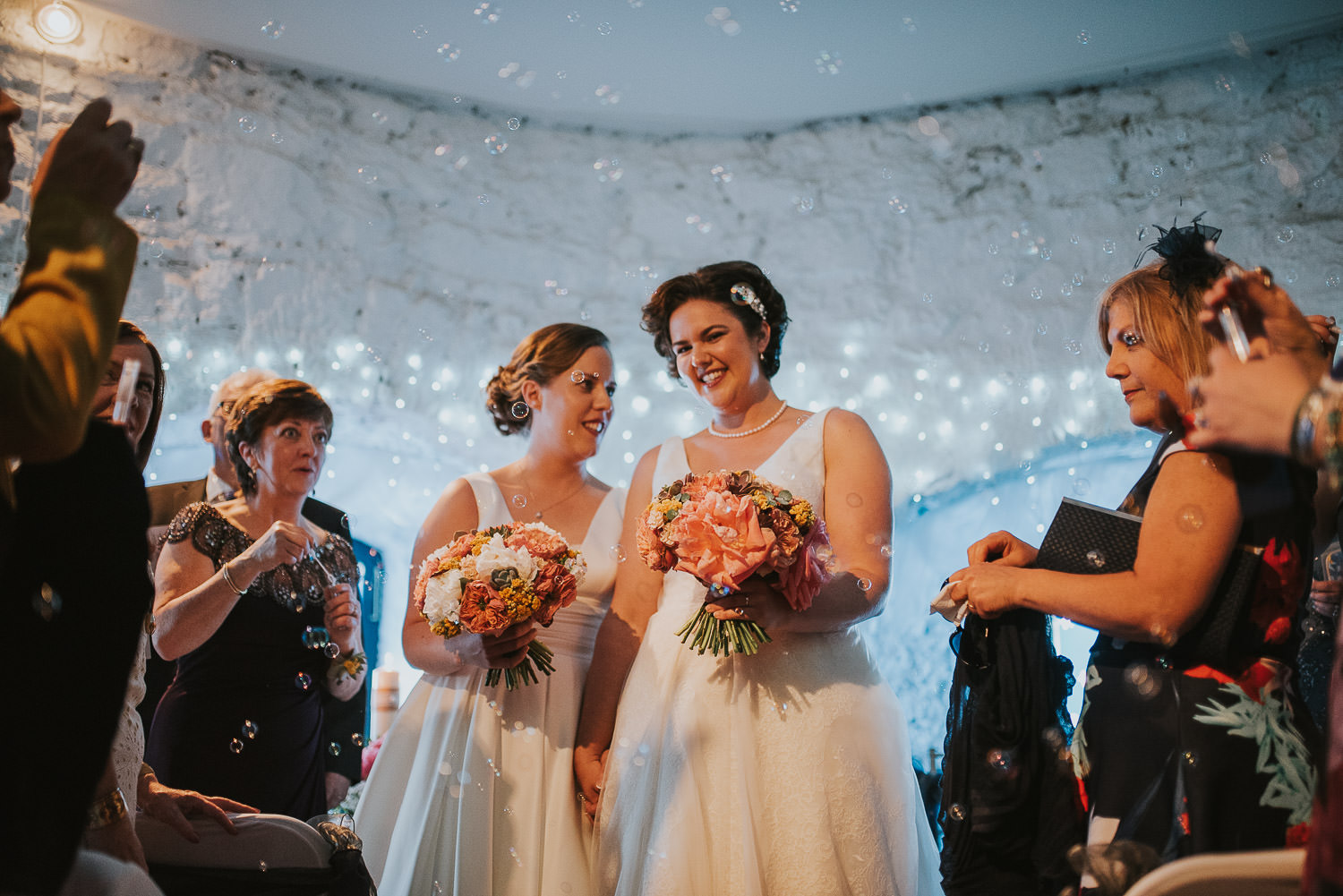 guests blowing bubbles as brides walk down the aisle