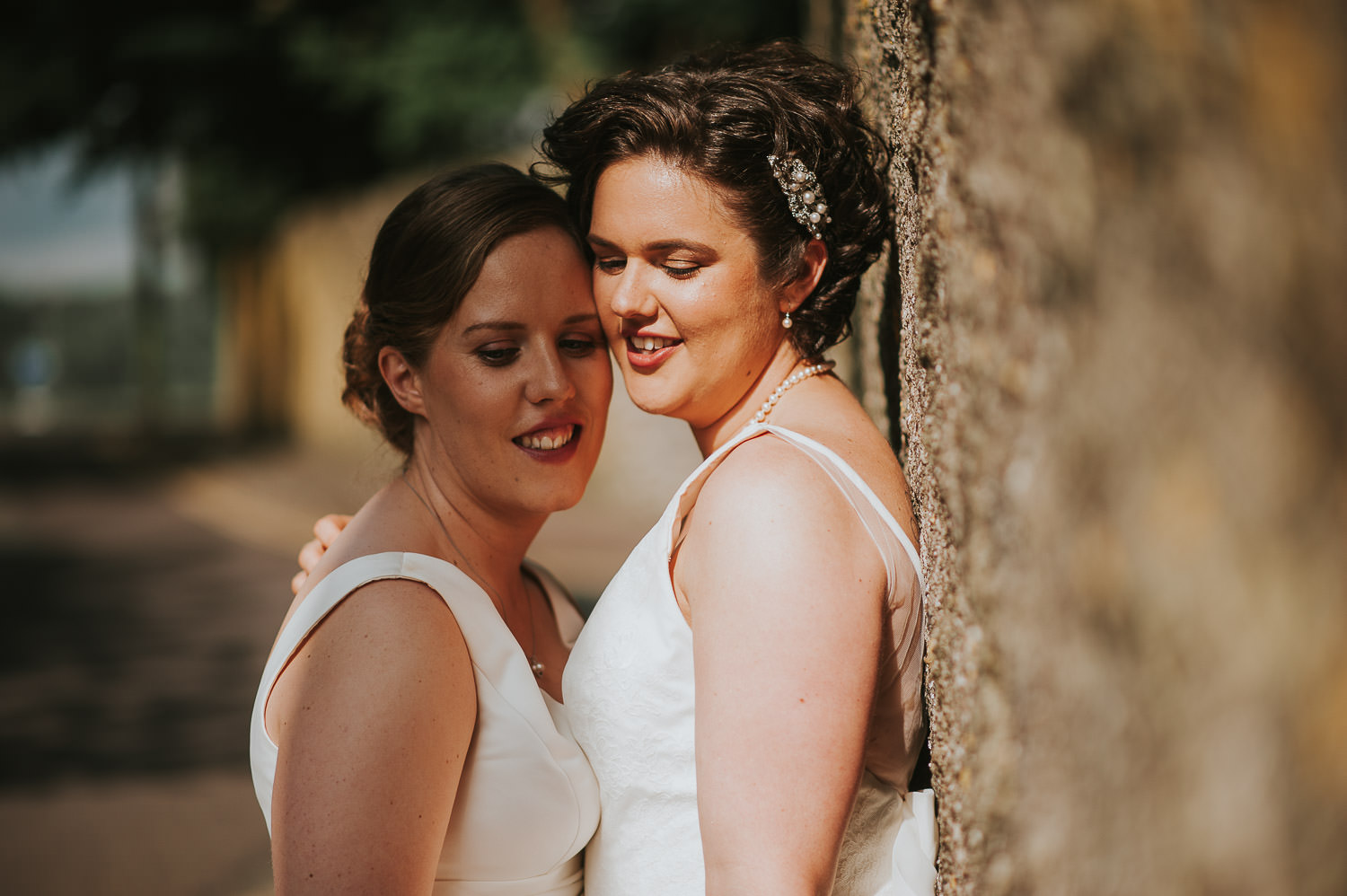 brides leaning in close in the afternoon sunshine