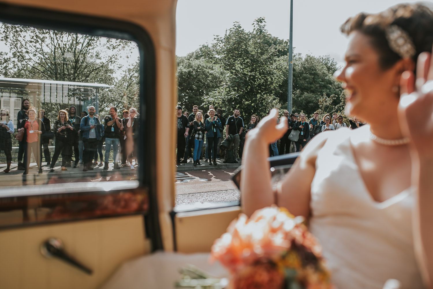 brides waving at people standing at a bus stop