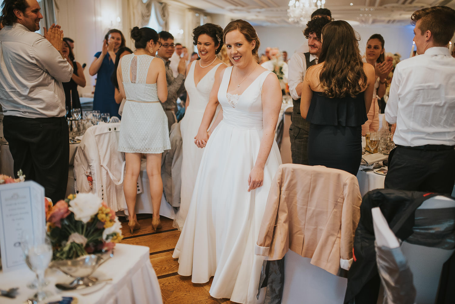 brides walking towards the top table